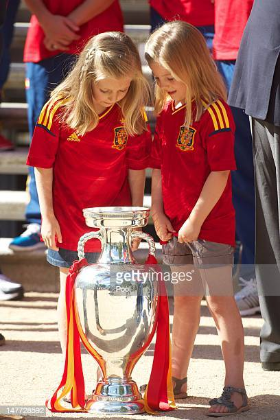 Princess Leonor of Spain and Princess Sofia of Spain look at the UEFA EURO 2012 trophy as King Juan Carlos I of Spain receives players of Spain's...