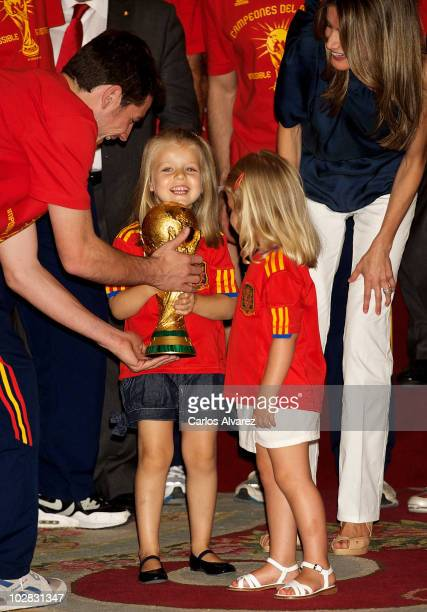 Princess Leonor of Spain holds the trophy with goalkeeper and captain Iker Casillas watched by Princess Sofia and Princess Letizia of Spain while the...