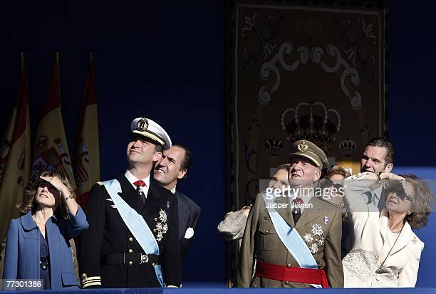Princess Letizia Crown Prince Felipe King Juan Carlos and Queen Sofia of Spain look at a parachutist landing during Spain's National Day Military...