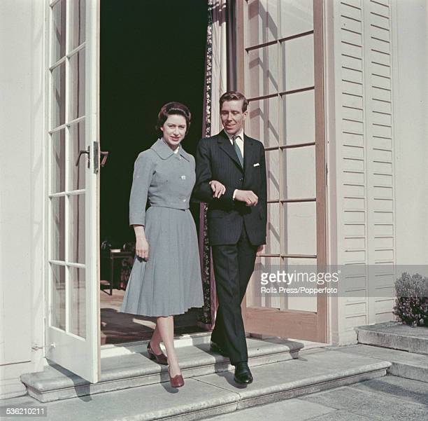 Princess Margaret and fiance Antony ArmstrongJones pictured stepping out through doors at the Royal Lodge Windsor after announcing their engagement...