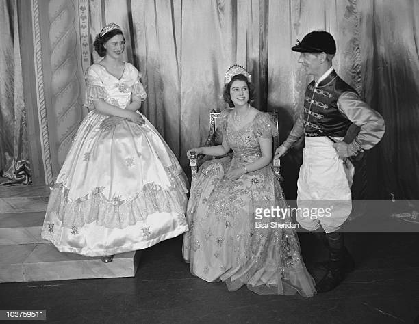 Princess Margaret and Princess Elizabeth both dressed in elaborate gowns pictured alongside a fellow performer during a royal pantomime production of...