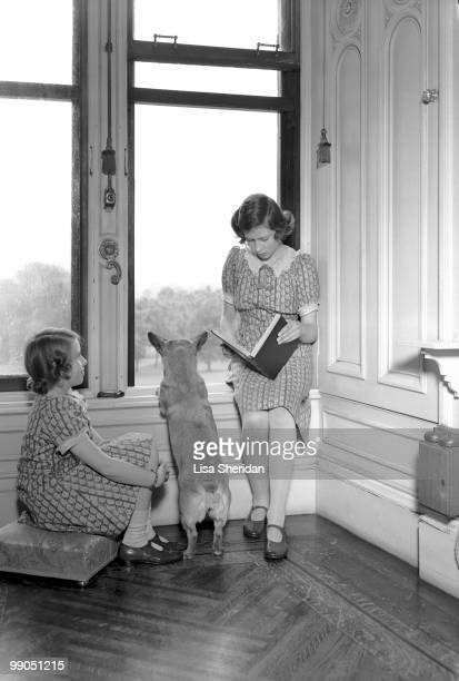 Princess Margaret and Princess Elizabeth pictured reading, while a corgi peers out of a window at Windsor Castle, Berkshire, Great Britain, 22 June...