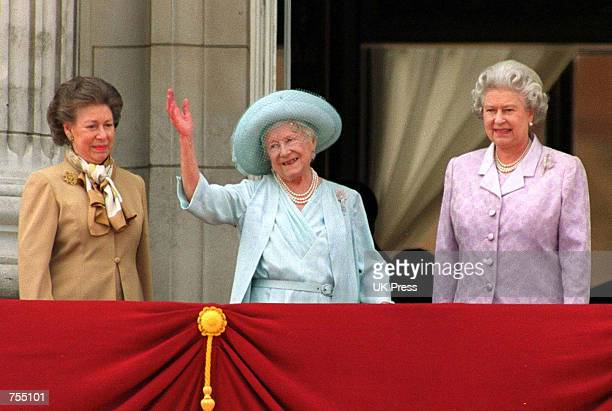 Princess Margaret and Queen Elizabeth stand next to the Queen Mother as she waves to admirers on the occassion of her 100th birthday celebration...