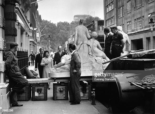 Princess Margaret Countess of Snowdon finds her way blocked by men moving a large statue across the pavement