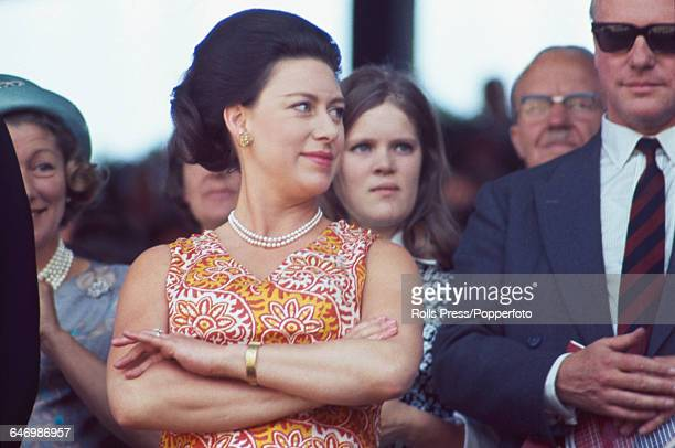 Princess Margaret, Countess of Snowdon pictured wearing a pearl necklace and orange, white and yellow patterned summer dress as she watches the...