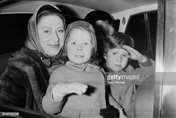 Princess Margaret, Countess of Snowdon sits in the backseat of a car with her children David and Sarah and their nanny Mabel Anderson, London, UK,...
