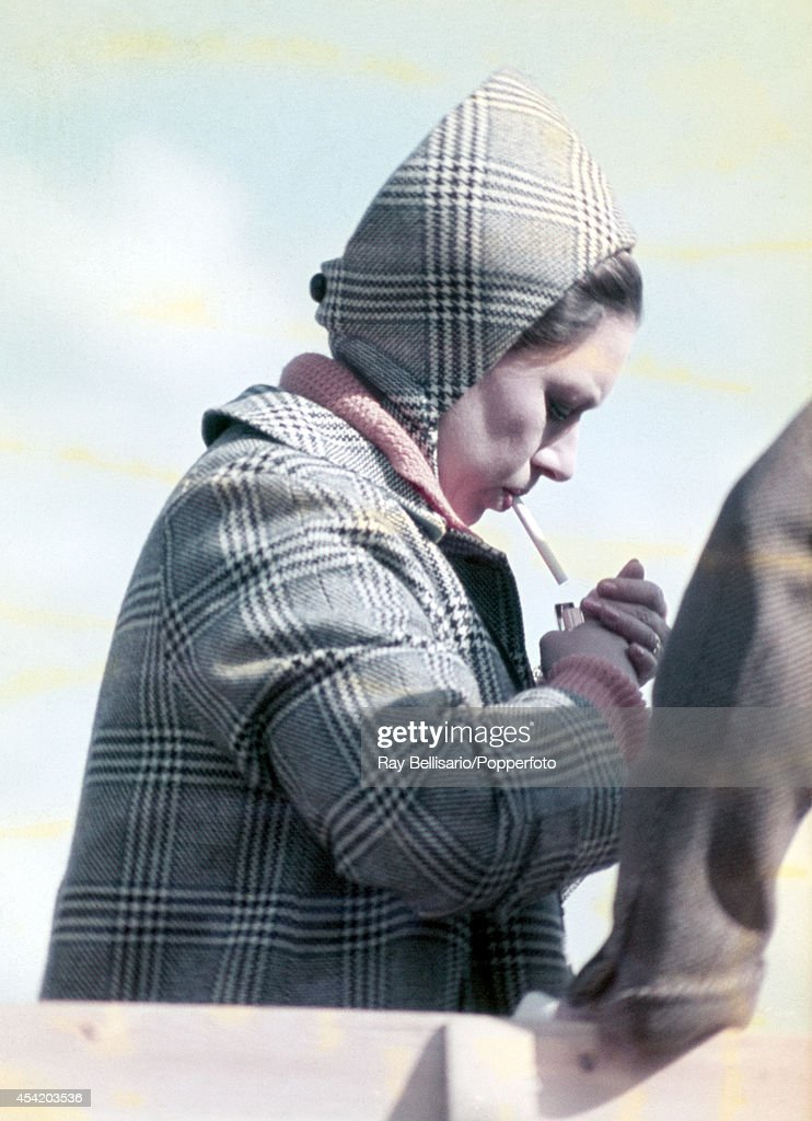 Princess Margaret lighting a cigarette during the Badminton Horse Trials in Gloucestershire on 18th April 1970. This image is one of a series taken by Ray Bellisario who was credited with being the 'original paparazzo' and someone who frequently upset the Royal Family with his informal and often unwelcome style of photography.