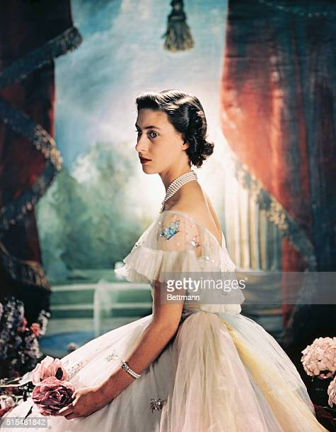 Princess Margaret Rose of England, is shown here seated and wearing a formal evening dress with sequence butterflies around the shoulder, and holding...