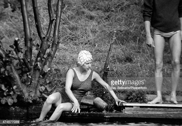 Princess Margaret sitting beside the lake at Sunninghill Park Windsor on 18th July 1964 This image is one of a series taken by Ray Bellisario who was...