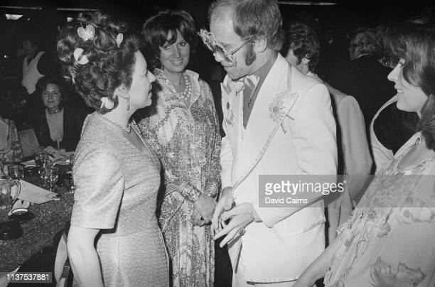 Princess Margaret speaking to singer-songwriter Elton John at an event in 1974. On the right is actress Nanette Newman.