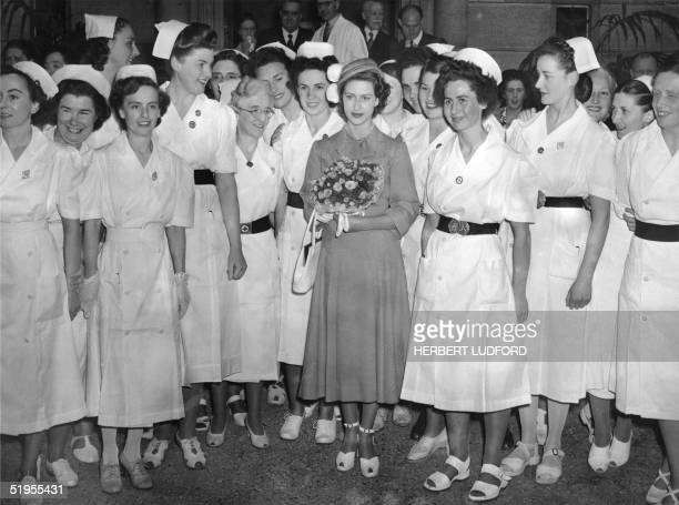 Princess Margaret the younger sister of future Britain's Queen Elizabeth II smiles 30 May 1949 among a group of nurses while she visits the Hertford...