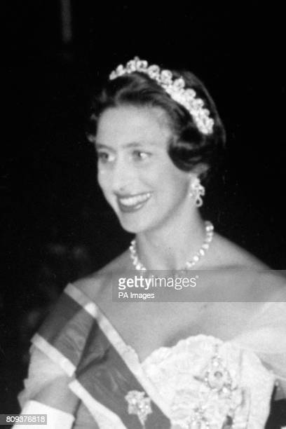 Princess Margaret wearing a crinoline evening gown slashed with the Ribbon of the Garter and the Cartier Halo Tiara arrives at the Sultan of...