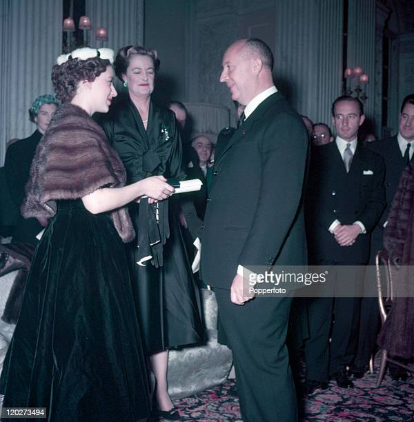 Princess Margaret with the Duchess of Marlborough behind presents Christian Dior with a scroll entitling him to Honorary Life Membership of the...