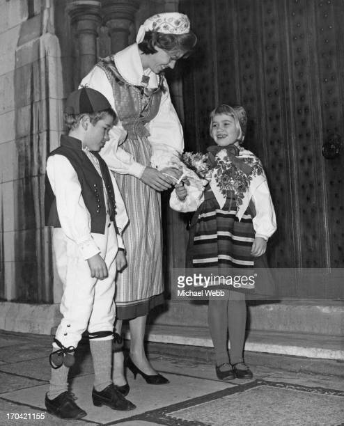 Princess Margaretha of Sweden in national costume receives a bouquet from twins Eva and Lars Sorensen, on her arrival at the Swedish Church Hall...