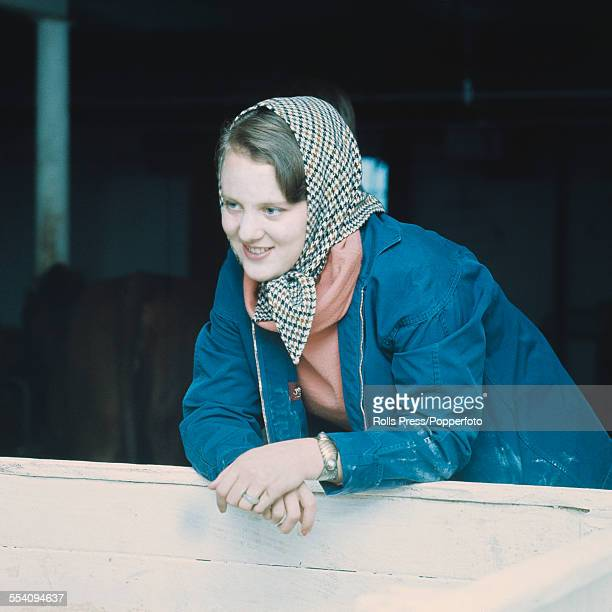 Princess Margrethe of Denmark pictured wearing a head scarf and functional blue jacket whilst leaning on the door of a farm cowshed on 21st July 1966...