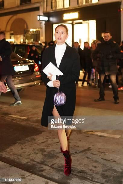 Princess Maria Olympia of Greece wears a white dress a purple bag red shoes a black coat outside Balmain during Paris Fashion Week Haute Couture...