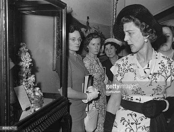 Princess Marina Duchess of Kent examines a porcelain Chelsea timepiece after opening the 10th Antique Dealers' Fair and Exhibition at Grosvenor House...