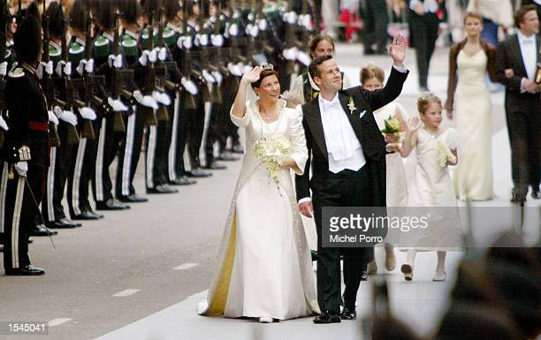 Princess Martha Louise of Norway and writer Ari Behn wave to crowds as they walk to the Stiftsgarden Palace after their wedding May 23 2002 in...