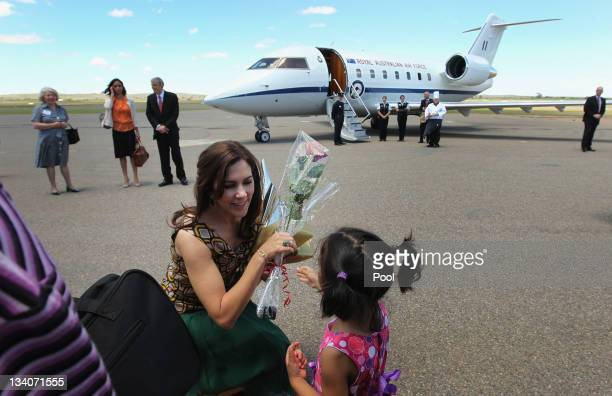 Princess Mary of Denmark accepts a rose from Maya Johns aged 3 as she farewells the crowd at Broken Hill airport after her visit to the Royal Flying...