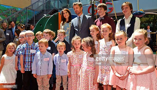 Princess Mary of Denmark and Prince Frederik of Denmark pose for a photo with identical twins during a visit to the Australian Twin Registry at the...