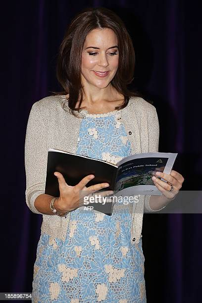 Princess Mary of Denmark reads a book received as a gift from a young school student at the launch of eSmart Homes Digital License an initiative of...
