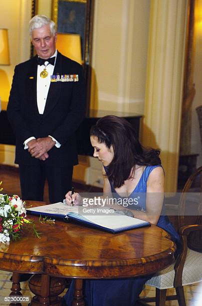 Princess Mary of Denmark signs the visitors book watched by Governor General Michael Jeffery, at Government House, March 8, 2005 in Canberra,...
