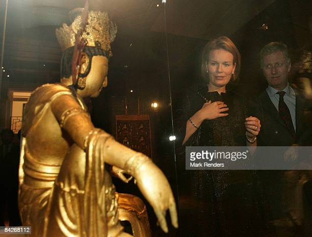 Princess Mathilde and Prince Philippe of Belgium view an exhibit during their visit to the Le Sourire de Bouddha exhibition at the Palais des...