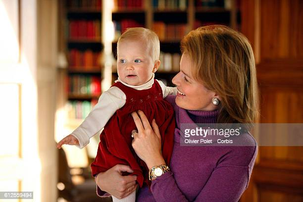 Princess Mathilde of Belgium holds Princess Eleonore in the lounge of the winter apartment