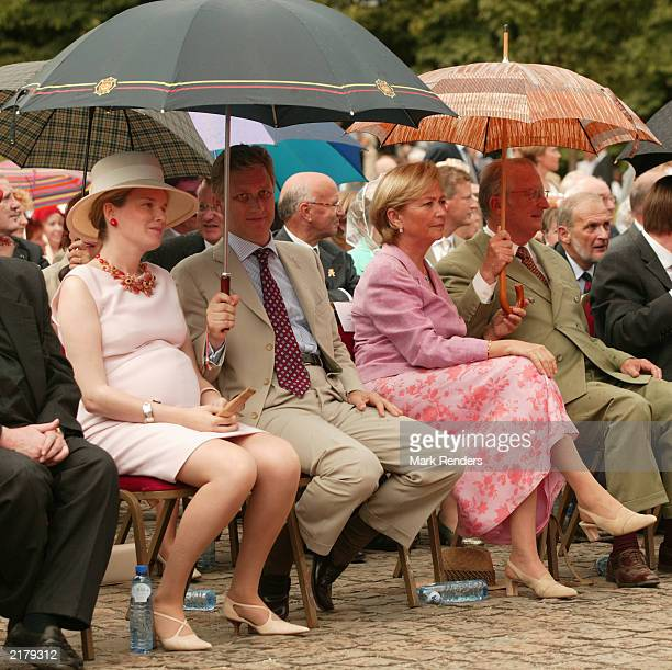 Princess Mathilde Prince Philippe Queen Paola and King Albert of Belgium seek shelter from the rain at the garden party to celebrate Albert's 10 year...