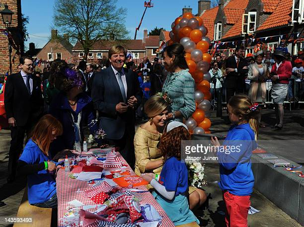 Princess Maxima of the Netherlands chats with a girl as Princess Margriet Prince WillemAlexander and Princess Marilene stand in the background during...