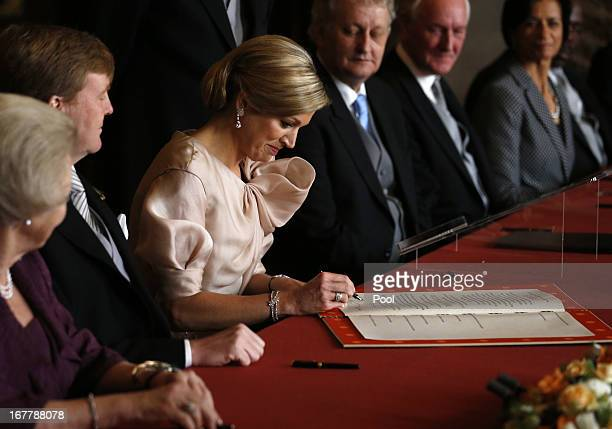 Princess Maxima of the Netherlands signs the Act of Abdication as Queen Beatrix of the Netherlands and her son Prince WillemAlexander of the...