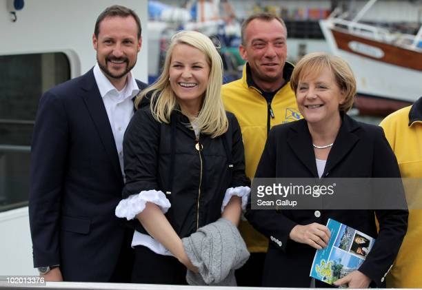 Princess Mette-Marit of Norway , Prince Haakon of Norway and German Chancellor Angela Merkel pose with sailors after returning from a boat trip to...