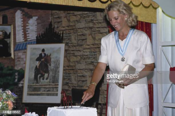 Princess Michael of Kent cuts a celebratory cake after awarding rosettes to members of the Horse Rangers Association , a London children's charity,...