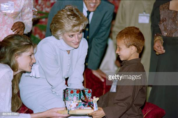 Princess of Wales Lady Diana offers a gift to cancer effected child after the variety show presented by the children at Khanum memorial cancer...