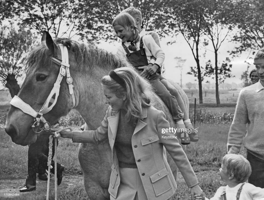 Princess Paola of Belgium (later Queen Paola of Belgium) holds the hand of her son, Prince Laurent of Belgium, whilst leading a horse carrying her children, Princess Astrid of Belgium and Prince Philippe of Belgium, whilst on a weekend away at a farm, 1967.