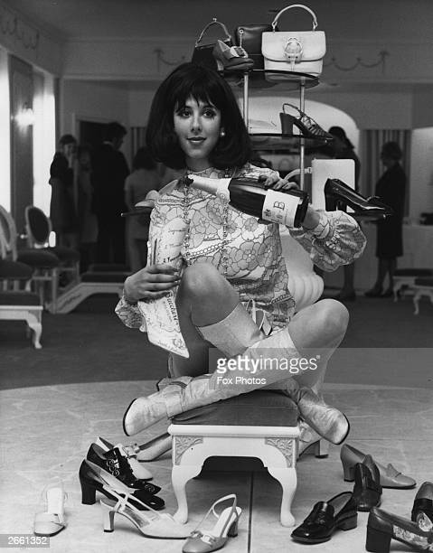 Princess Premila of Rajpipla perched on a foot stool holding a bottle of JB champagne at the opening of the Pinet Shoe Salon London 27th May 1969