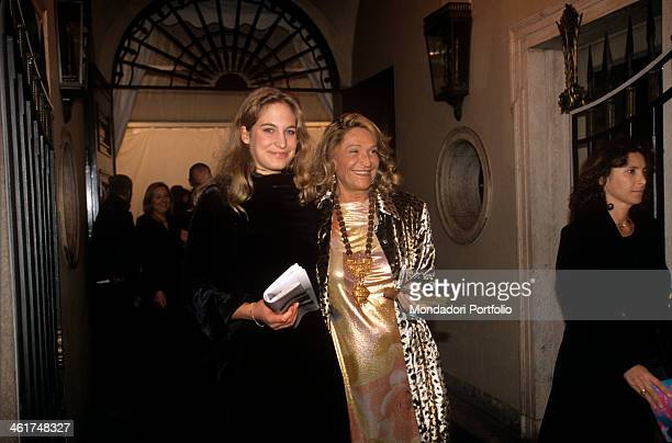 Princess Robinia Mentasti in a dark coat and fashion designer Marta Marzotto sporting a gold shining long dress and a flashy medallion cross the iron...