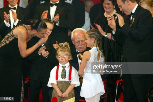 Princess Stephanie of Monaco kisses her son Louis as her daughters Camille and Pauline give a special award to their grandfather Prince Rainier III...