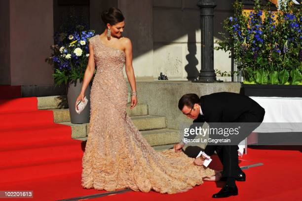 Princess Victoria is helped with her dress by fiance Daniel Westling during the Government PreWedding Dinner for Crown Princess Victoria of Sweden...