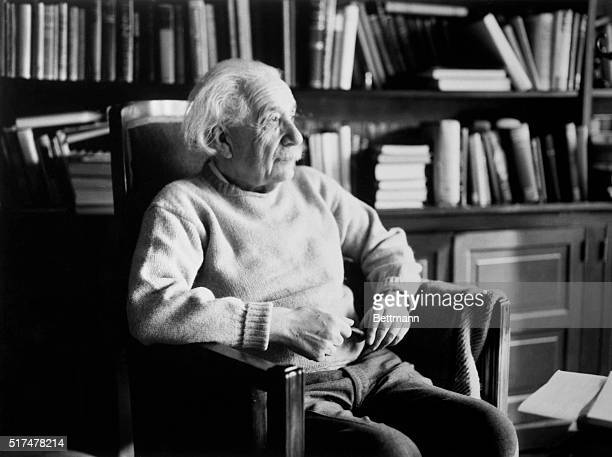 Physicist Albert Einstein seated in bookfilled office holding a pipe