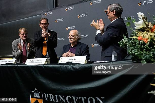 Princeton University professor F. Duncan Haldane , who was awarded the 2016 Nobel Prize in Physics, is applauded by Lyman Page, chair of the Physics...
