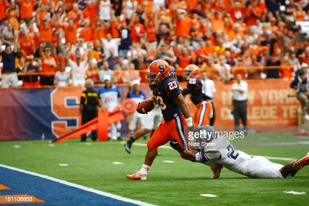 PrinceTyson Gulley scores a touchdown for the Syracuse Orange as he is chased by Ibraheim Campbell of the Northwestern Wildcats during the game on...