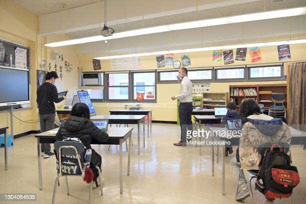 Principal Ben Geballe helps students settle into a classroom at Sun Yat Sen M.S. 131 on February 25, 2021 in New York City. New York City middle...