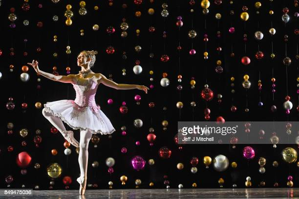 Principal dancer Constance Devernay, dressed in the sugar plum fairy costume poses against a backdrop of Christmas baubles at the Tramway on...