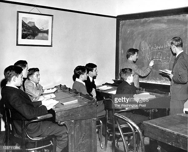FILE Principal Ernest L Kendall checks a math problem being worked out by Robert P Curtis of Silver Spring inside the classroom at the US Capitol...