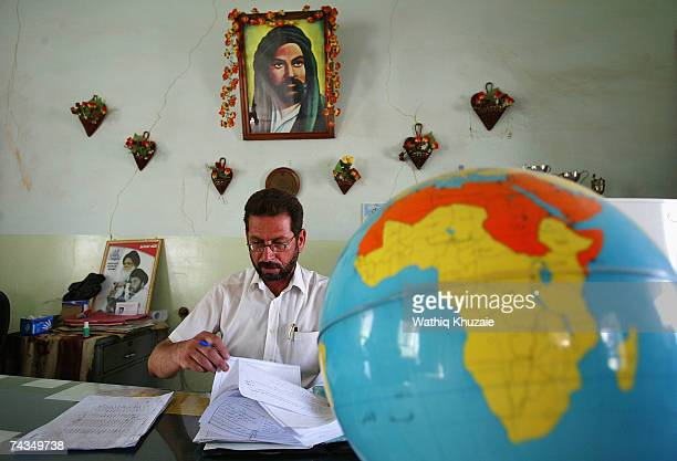 A principle of an Iraqi primary school sits under a picture of Imam Ali on May 29 2007 in a school in the Sadr city neighborhood of Baghdad Iraq The...