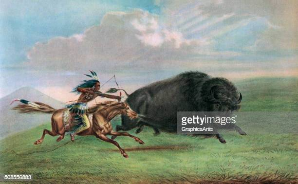 Print of a buffalo hunt after a painting by George Catlin depicting a Plains warrior on horseback hunting a bison in the American West c 1920 Screen...