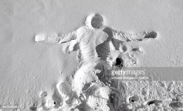 Print Of Human Body With Footprints On Snow