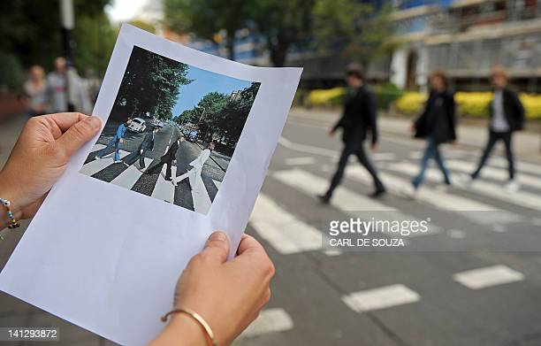 A print of the famous Abbey Road Beatles record cover is pictured at the same pedestrian crossing on Abbey Road in north London on August 7 2009 Fans...