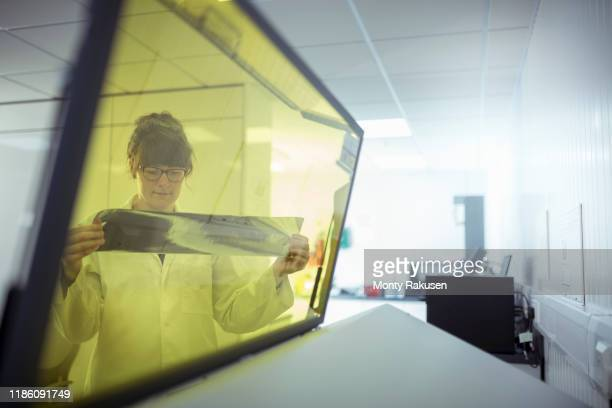 print scientist examining sample laser etched foil in print factory - yellow stock pictures, royalty-free photos & images